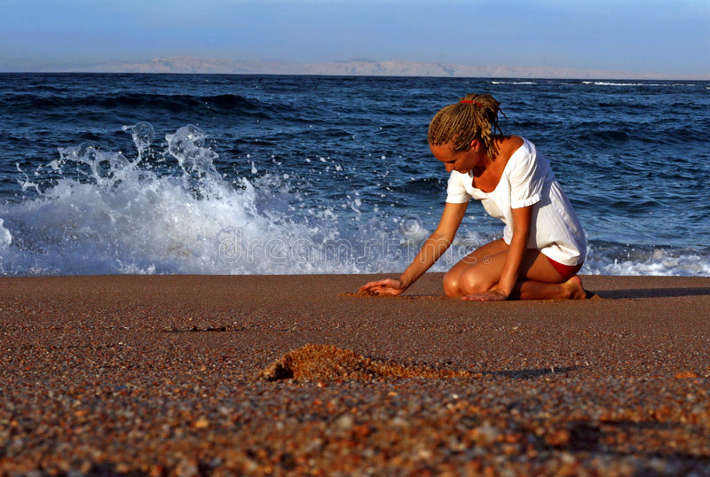 Sea, sun and a girl. A girl playing with sand at the seaside stock images
