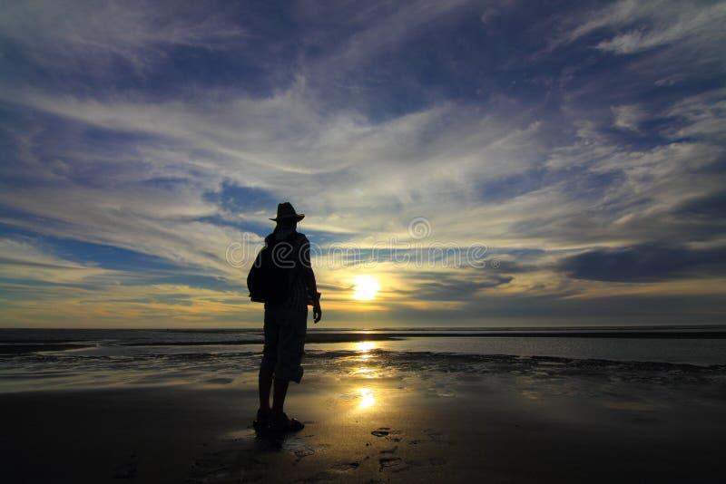 Sea sunset. The man seeing ocean in sunset stock photo