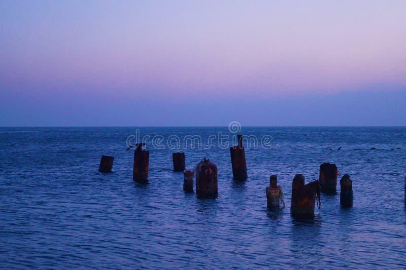Sea sunset. On a broken pier stock photo
