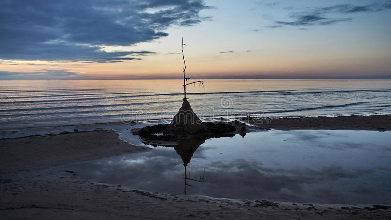 Sea clouds after sunset and sand castle stock photo