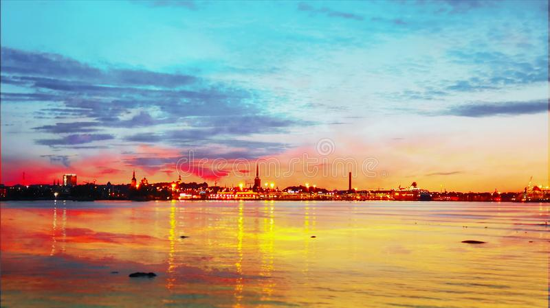 Sea sunset sunlight night sky moon light skyline evening light reflection on seawater gold summer sunset city panorama on horizon. Old town Tallinn   nature stock photography