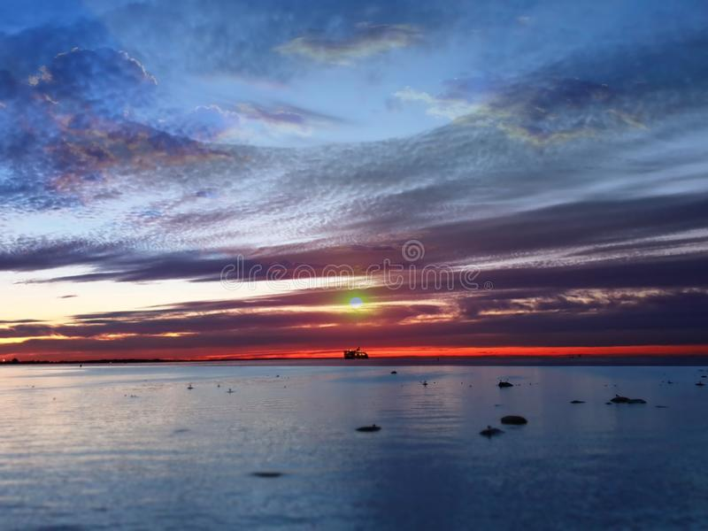 Sea sunset sunlight night sky moon light skyline evening light reflection on seawater gold summer sunset city panorama on horizon. Old town Tallinn   nature stock image