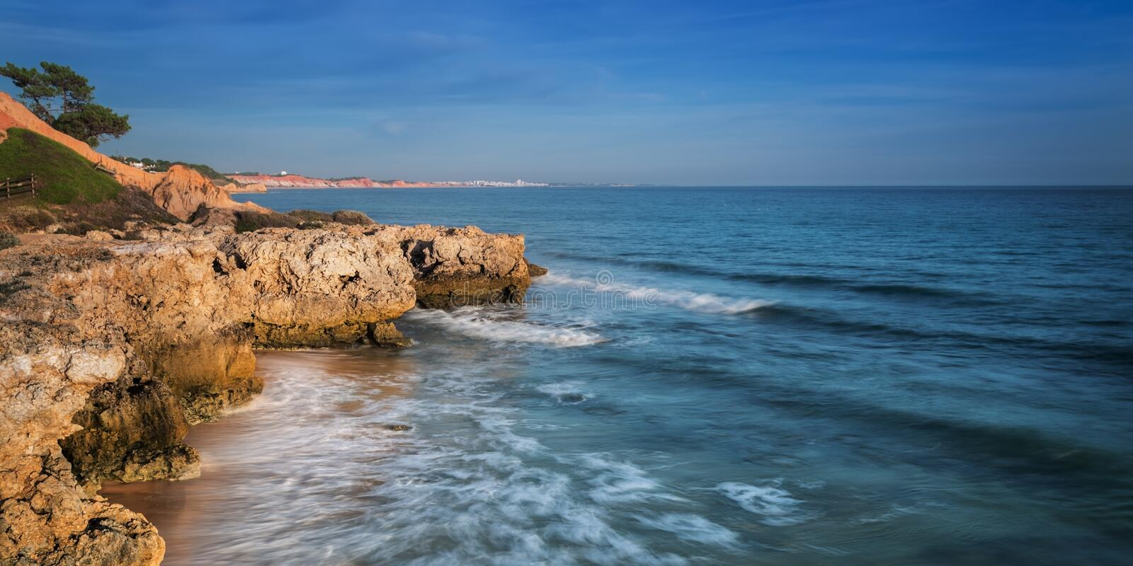 Sea surf in Albufeira beach and mountain in Portugal. stock image