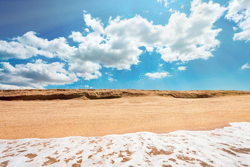 Sea surf with clear water and yellow hot sand, summer beach with clouds stock photo