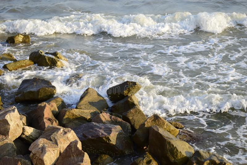 Sea surf and rocks on the coast. Wet stones and waves royalty free stock photography
