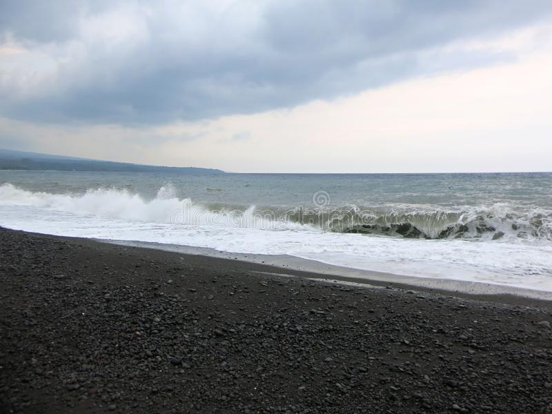 Sea surf and waves crashing against a black sand beach in Bali. royalty free stock photos
