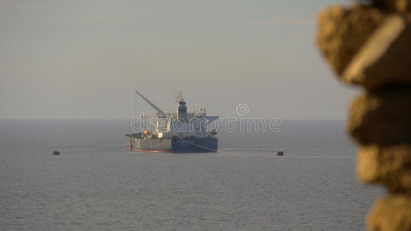 Sea tanker at parking near coastline with ancient wall stock photo