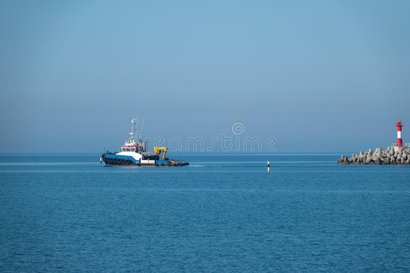 The sea tug comes out of the harbor royalty free stock image
