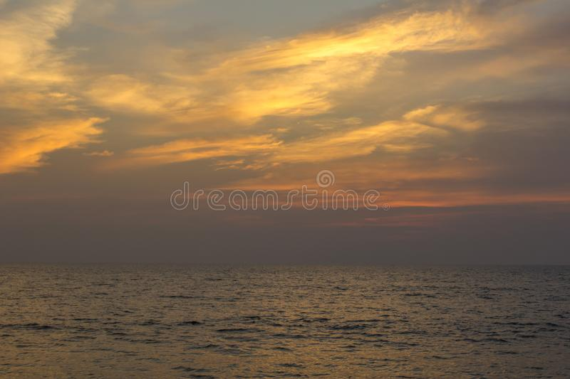 Sea under a purple sunset sky with bright orange clouds. A sea under a purple sunset sky with bright orange clouds royalty free stock photos