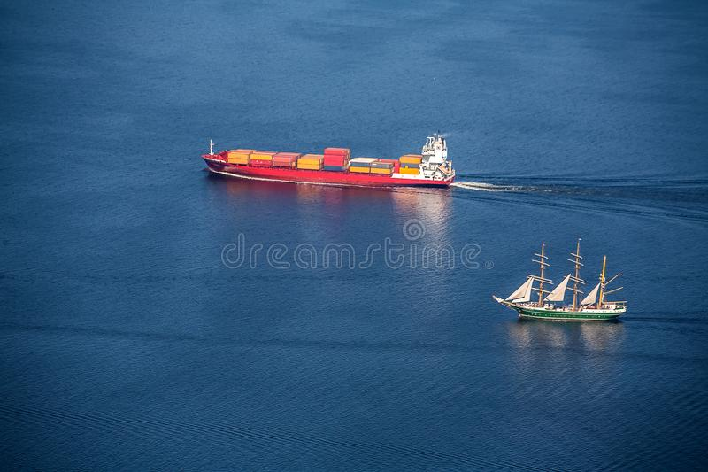 A sea vessel is a container ship and Tall ship at full speed in the open sea. View from above.n royalty free stock photo