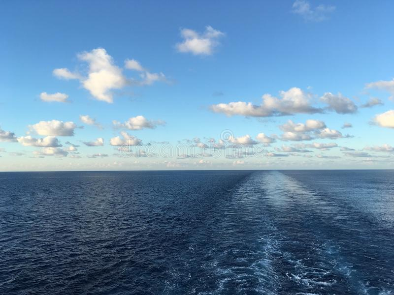 Sea view from back deck of a ship. Sea view from a balcony of a cruise ship sailing at the calm sea during bright day with some clouds stock photo