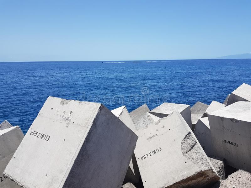 Sea and island view at Las Cristianos in Tenerife. Sea view with man made concrete cube blocks at Las Cristianos in Tenerife on a beautiful sunny day with blue stock image