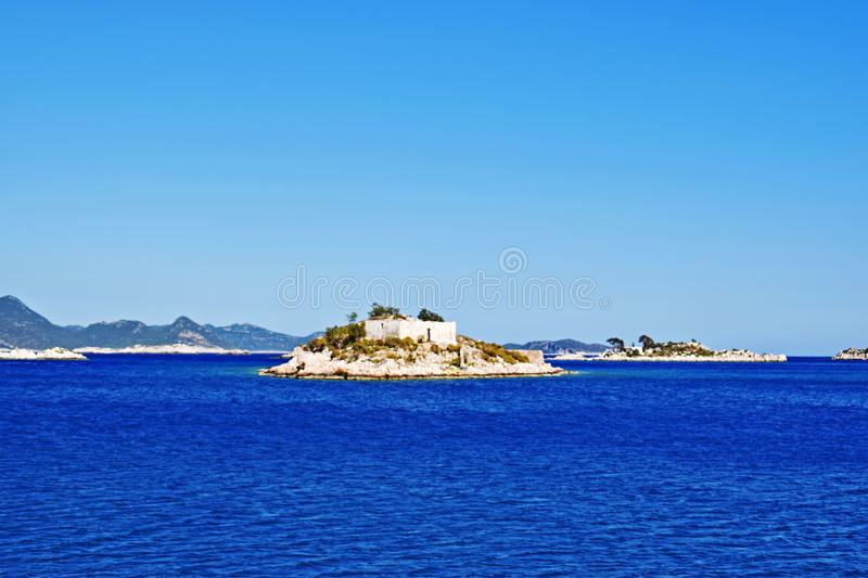 A sea view on a summer`s day. Picturesque sea view of the crystal clear blue water of the Mediterranean sea surrounding the small islands and the mountains in royalty free stock photography