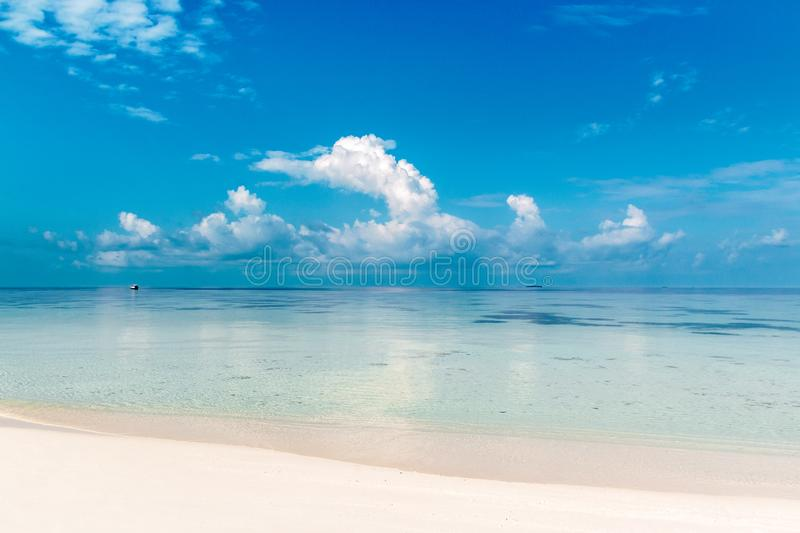Sea view from a white beach during a sunny day in the maldives. Landscape, no people. View of the clear blue water in a tropical destination royalty free stock photography