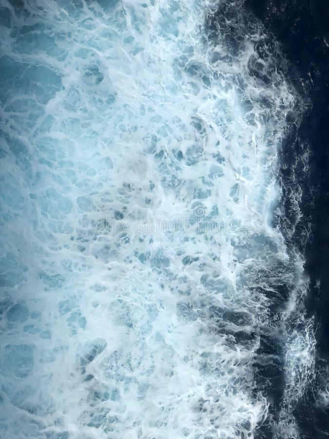 Sea water waves with foamy wave. Sea water with foamy waves being made a a cruise ship sails in the North Atlantic ocean royalty free stock images