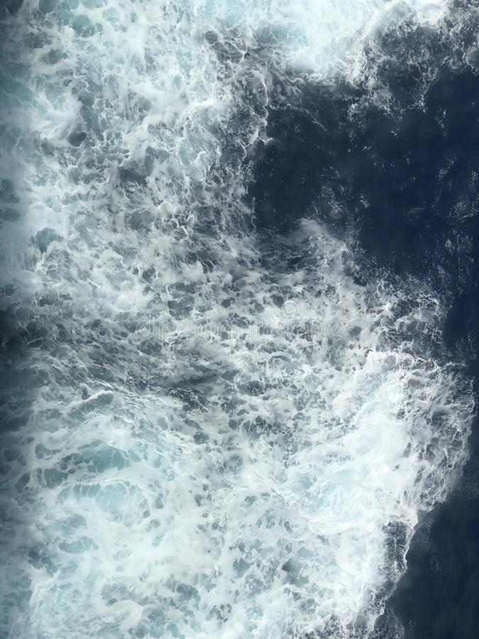 Sea water waves with foamy wave. Sea water with foamy waves being made a a cruise ship sails in the North Atlantic ocean royalty free stock photography