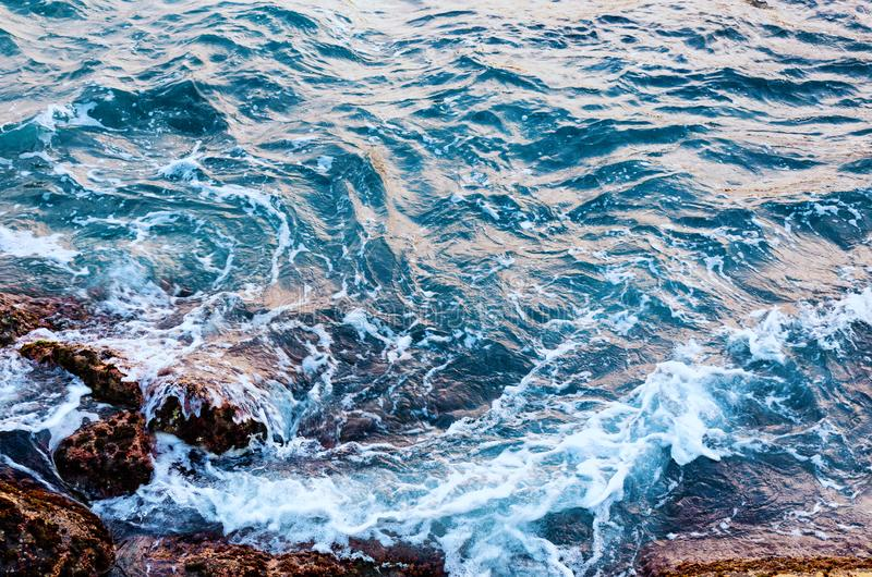 Sea water hits stone beach, wave and beach, nature background concept. Photo with motion blur royalty free stock images