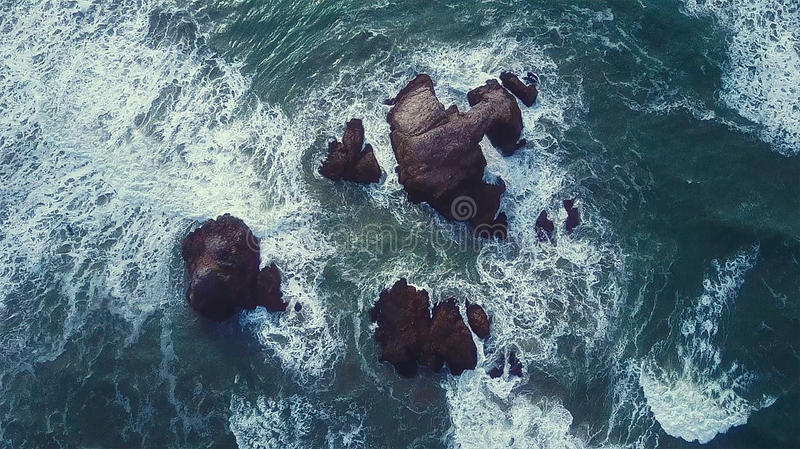 Sea water splashing against rocks royalty free stock photo