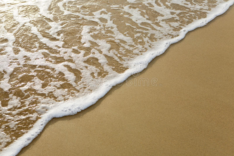 Sea wave. Closeup of sand and wave on seashore at sunny day royalty free stock photography
