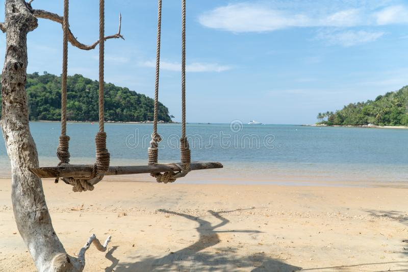 Sea wave on the beach and Wooden swing hang. Under a tree royalty free stock photo