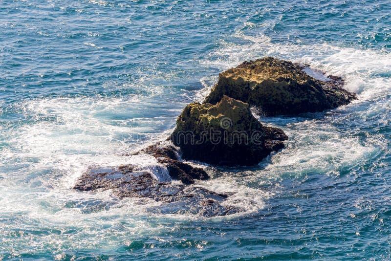 Sea wave breaks on beach rocks landscape. Sea waves crash and splash on rocks. Beach rock sea wave breaking. Coast, water, nature, stone, coastline, foam stock image