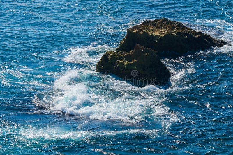 Sea wave breaks on beach rocks landscape. Sea waves crash and splash on rocks. Beach rock sea wave breaking. Coast, view, travel, rocky, beauty, cliff, white stock photos