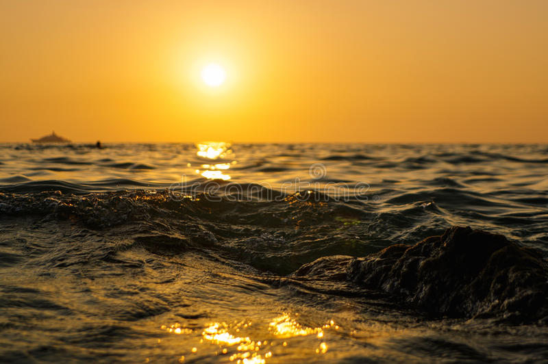 Sea wave close up at sunset time with red and orange sun reflection on the water. nature abstract blurred background. Phuket royalty free stock image
