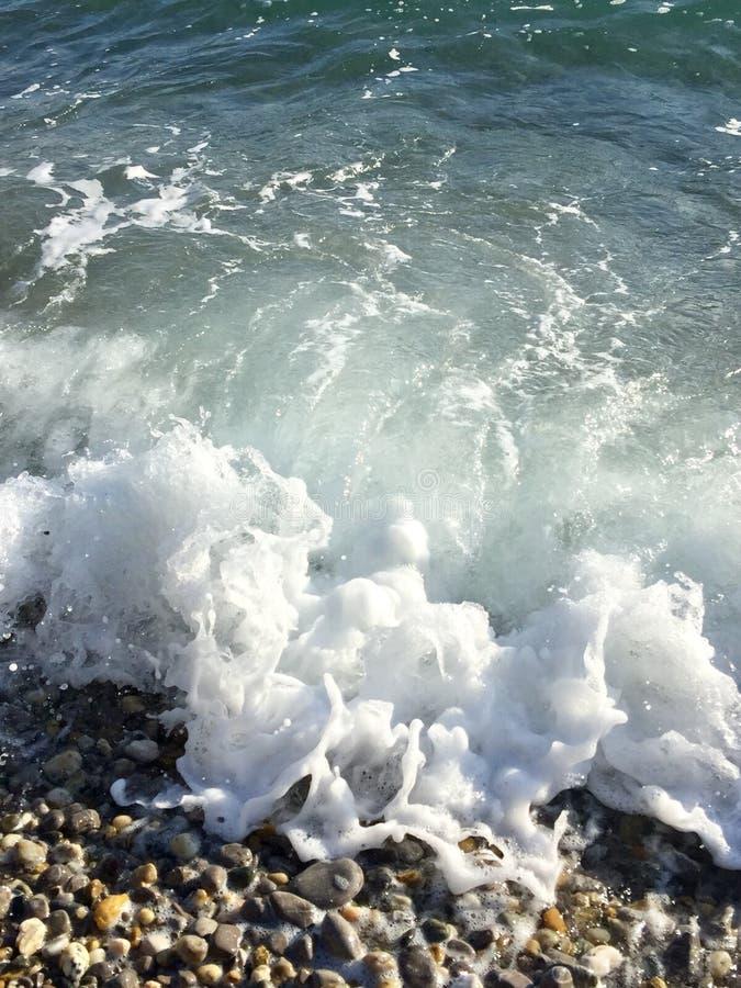 Sea wave. Making foam on pebble beach royalty free stock photography
