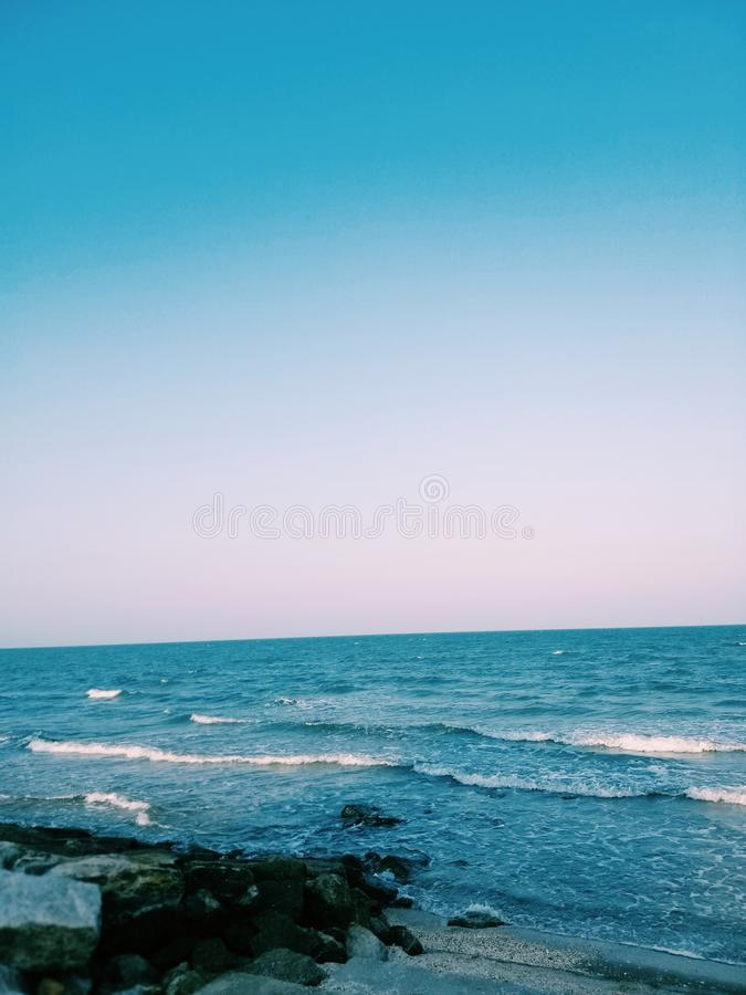 Sea wave with Blue sea and clearly sky. Evening light. Rock beach. Waveblue, summer, travel, relax, peace, seawave, bluesea, clearlysky royalty free stock image