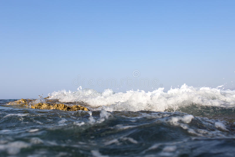 Sea wave splashing over the shore rocks with a high sea spray.  stock photography