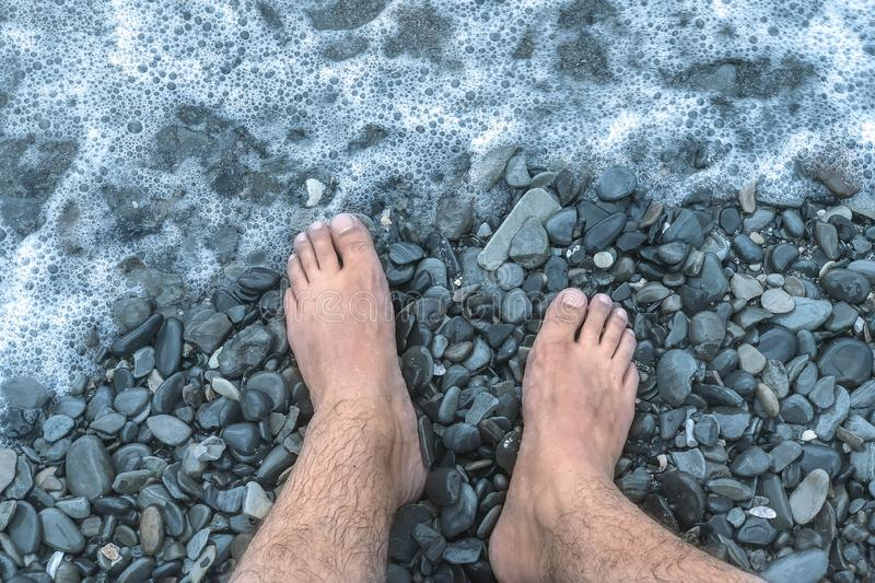 A sea wave on a stone beach covered with the rocks, male feet in the splashing wave. stock photo