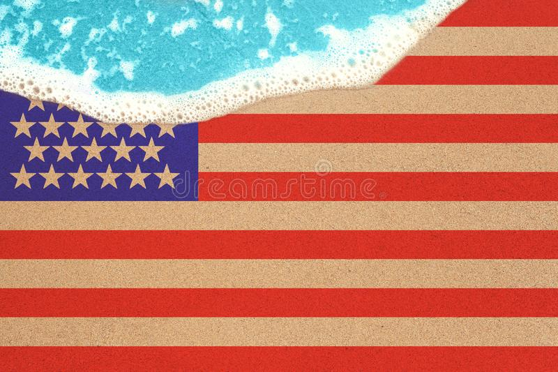 Sea wave on the sunny sandy beach with flag USA. View from top on surf.  stock photo