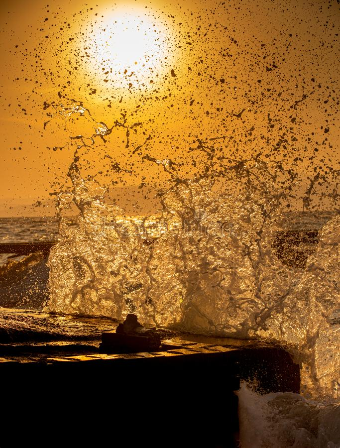 Sea waves breaking at beach pier . Sunlight penetrating through splashes.  stock images