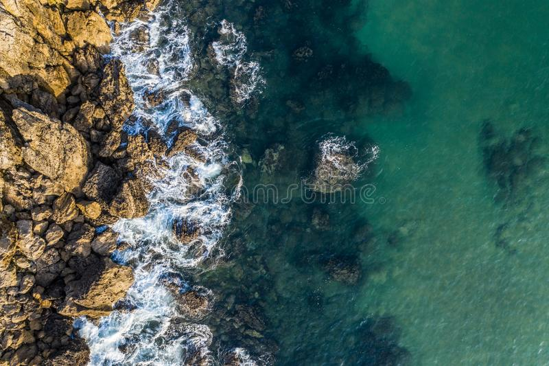 Sea waves breaking in the reefs and coast of Sonabia, Spain, Cantabrian sea. Drone aerial view royalty free stock photography