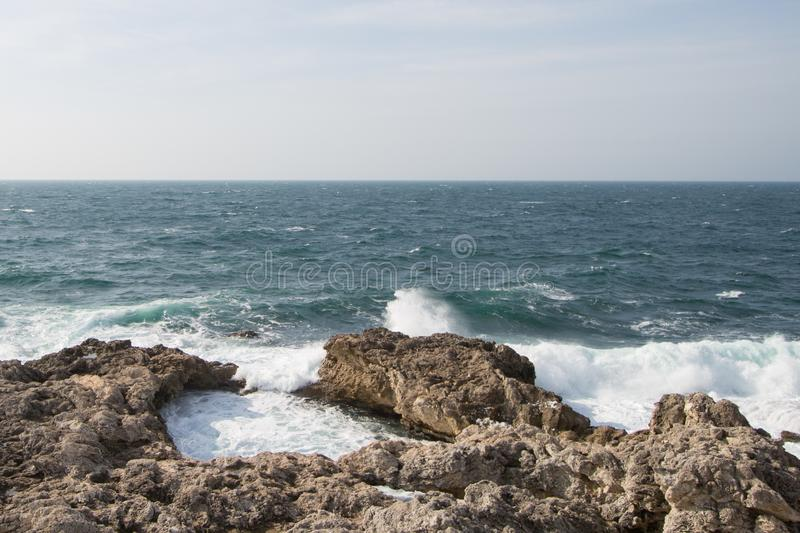 Sea waves crashing against the rocks. Day stock photography