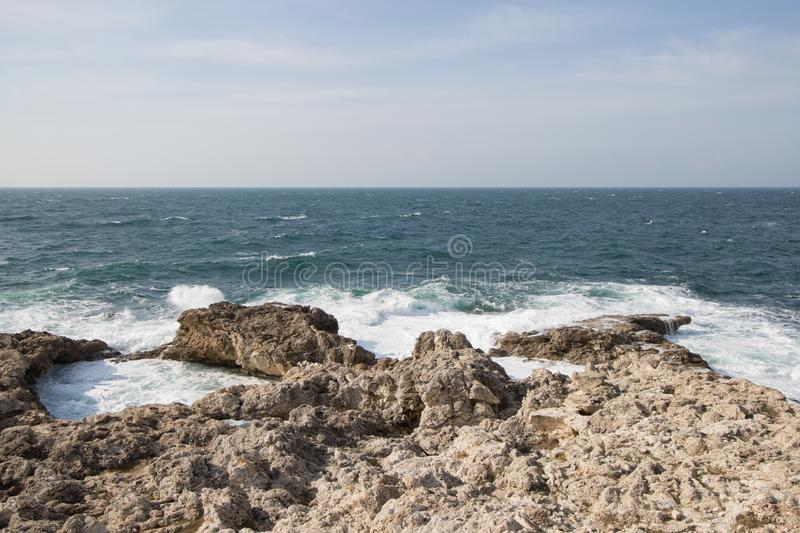 Sea waves crashing against the rocks. Day royalty free stock photo