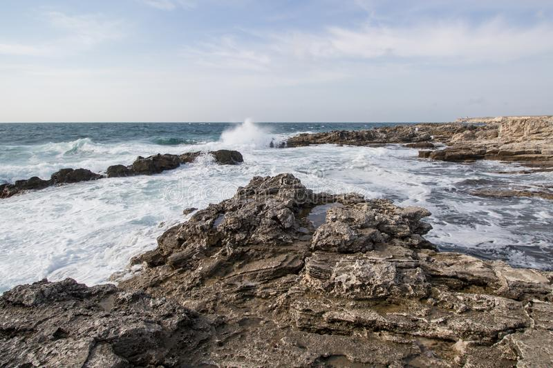 Sea waves crashing against the rocks. Day royalty free stock image