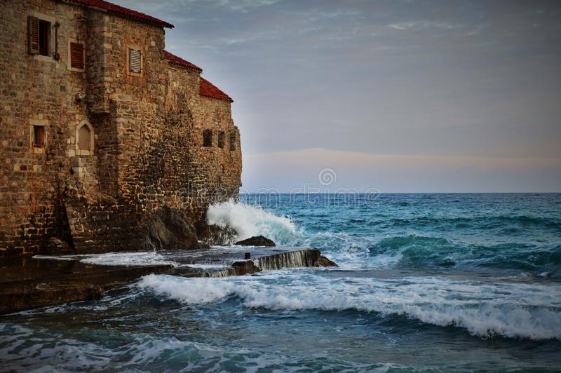 Sea waves crashing on historical building. Place where sea meets historical town and crashes its strong waves to the side of an old building royalty free stock photography