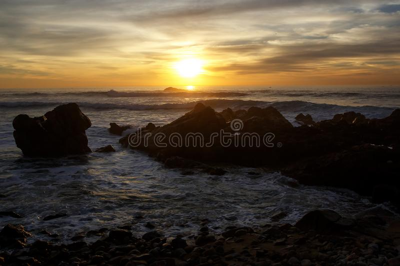 Sea waves crashing onto the rocks on sunset stock images