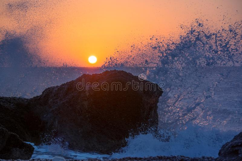 Sea waves crushing and splashing on the rocks on a tropical beach, in beautiful warm sunset light stock photo
