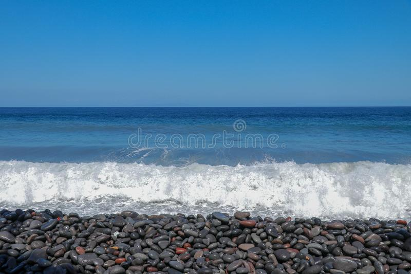 Sea waves hitting the stony coast. Waves turn into sea foam. Frothy sea water and bubbles. The Azores kill water. Background stock photo