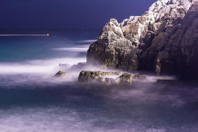 Sea waves lash line impact rock on the beach in night.  royalty free stock photography