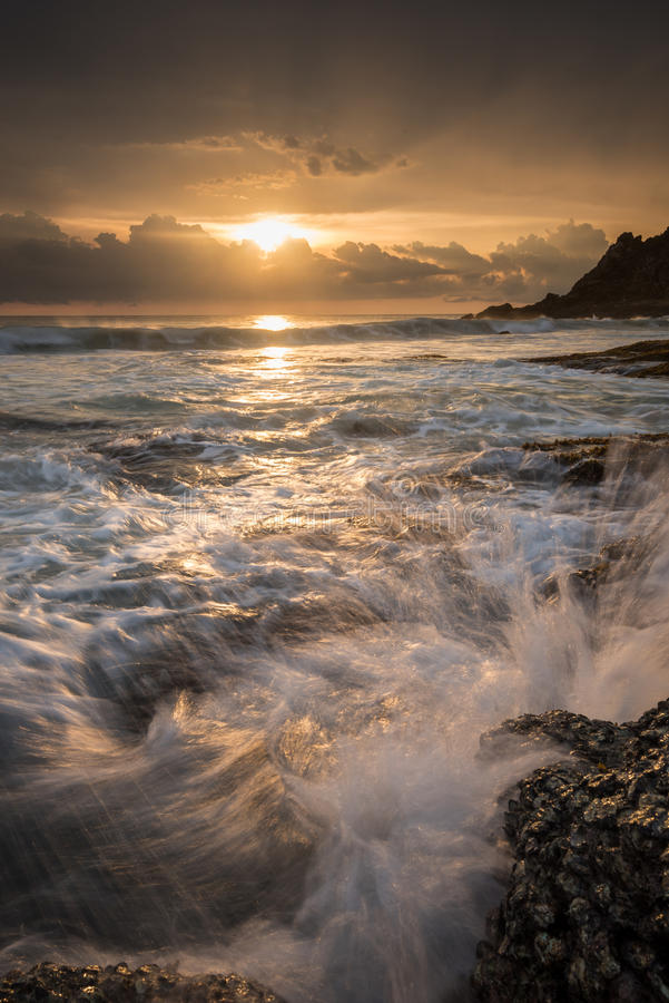 Sea waves lash line impact rock on the beach. At sunset stock image