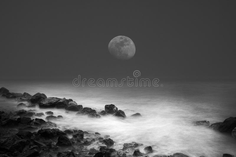 Sea waves rock and the moon. In the night stock photography