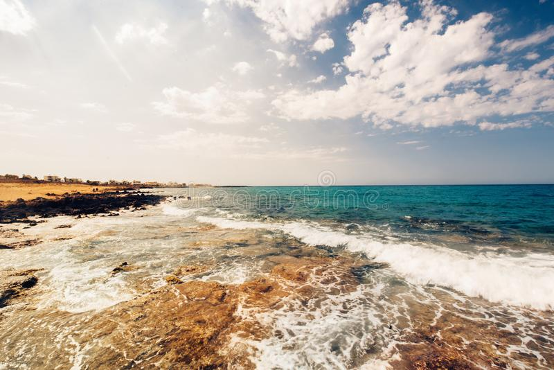 Sea waves and rocks at sunset, creamy water and clear skies on a beautiful summer day stock photography