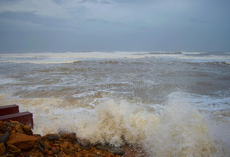 Sea Waves striking Rocks on Shore and Sprinkle of Water Droplets in Air with Cloudy Sky - Vayu Cyclone 2019 royalty free stock image