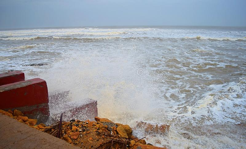 Sea Waves striking Stairs and Rocks on Shore and Shower of Water Droplets in Air with Cloudy Sky - Vayu Cyclone 2019 stock image