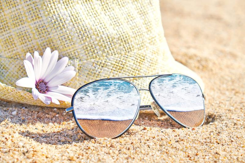 Sea waves in stylish mirrored sunglasses on sand. Tropical summer vacation. Summer day on beach royalty free stock image