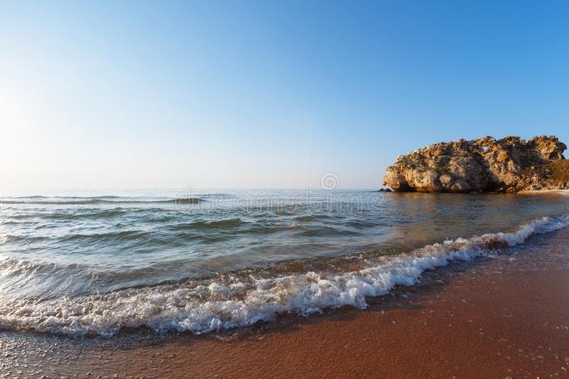 Sea with waves in a wild bay at sunset.  royalty free stock photos