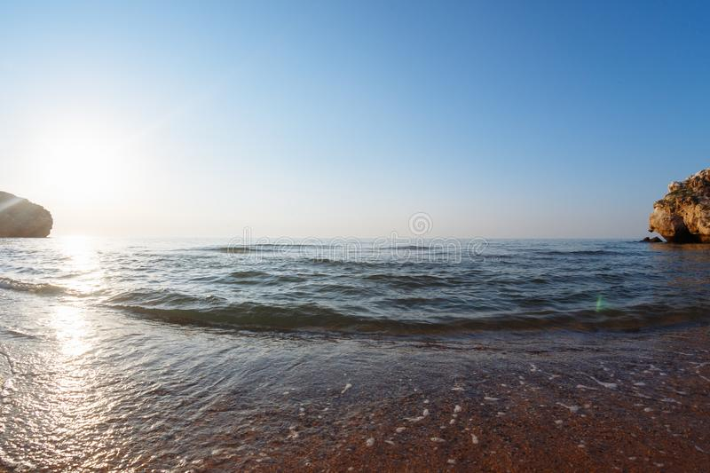 Sea with waves in a wild bay at sunset.  stock photo